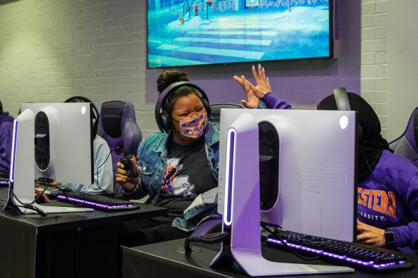 Two female students high-five each other while sitting at desktop PCs.