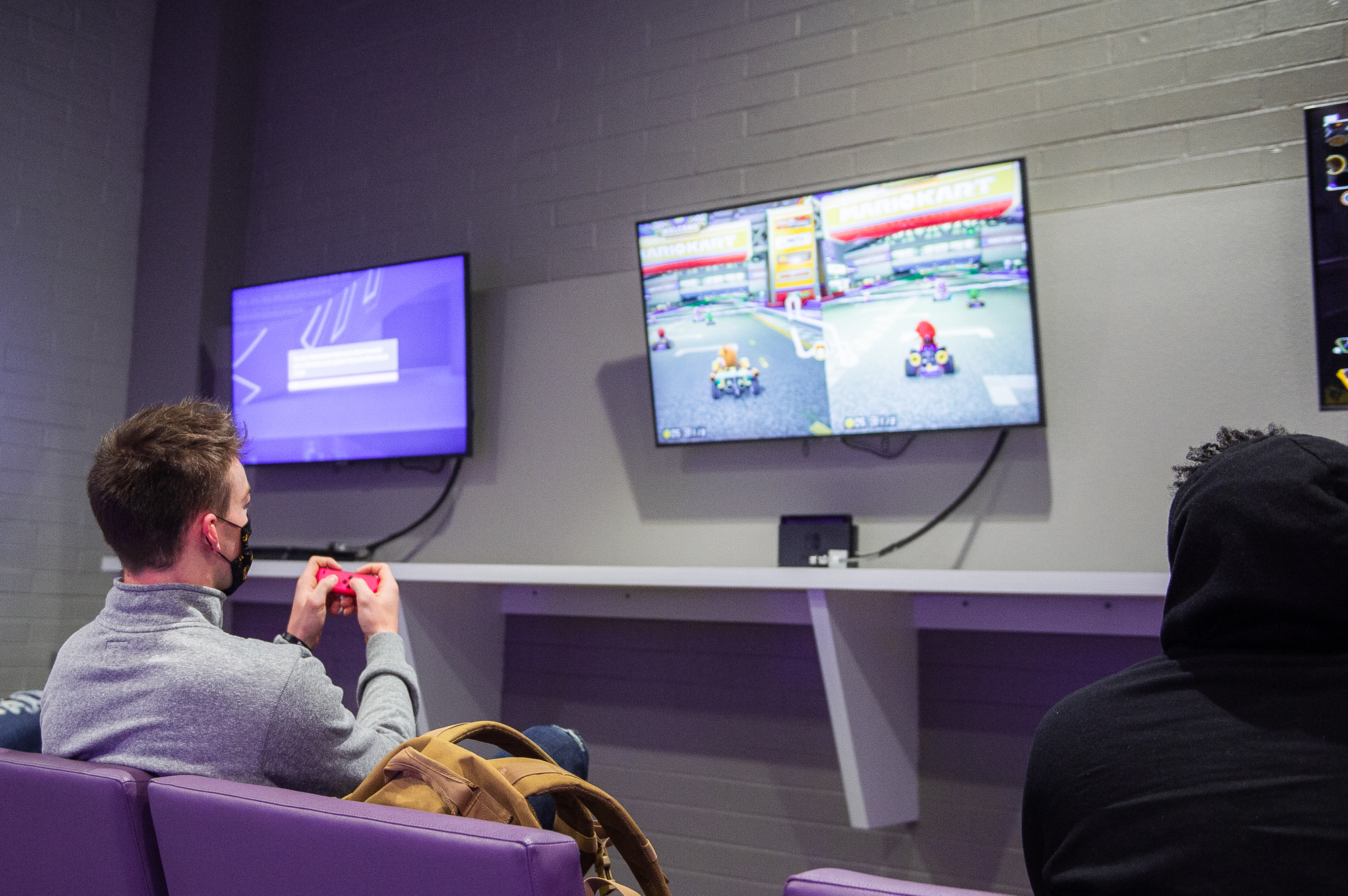 Two male students play Mario Kart.