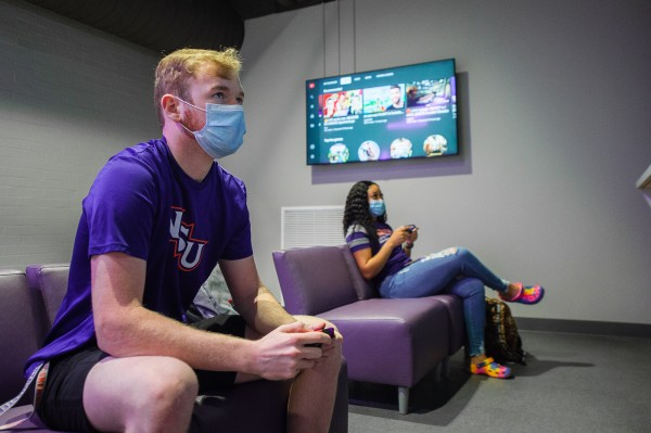 A masked male and female student sit holding game controllers while facing an off-camera screen.