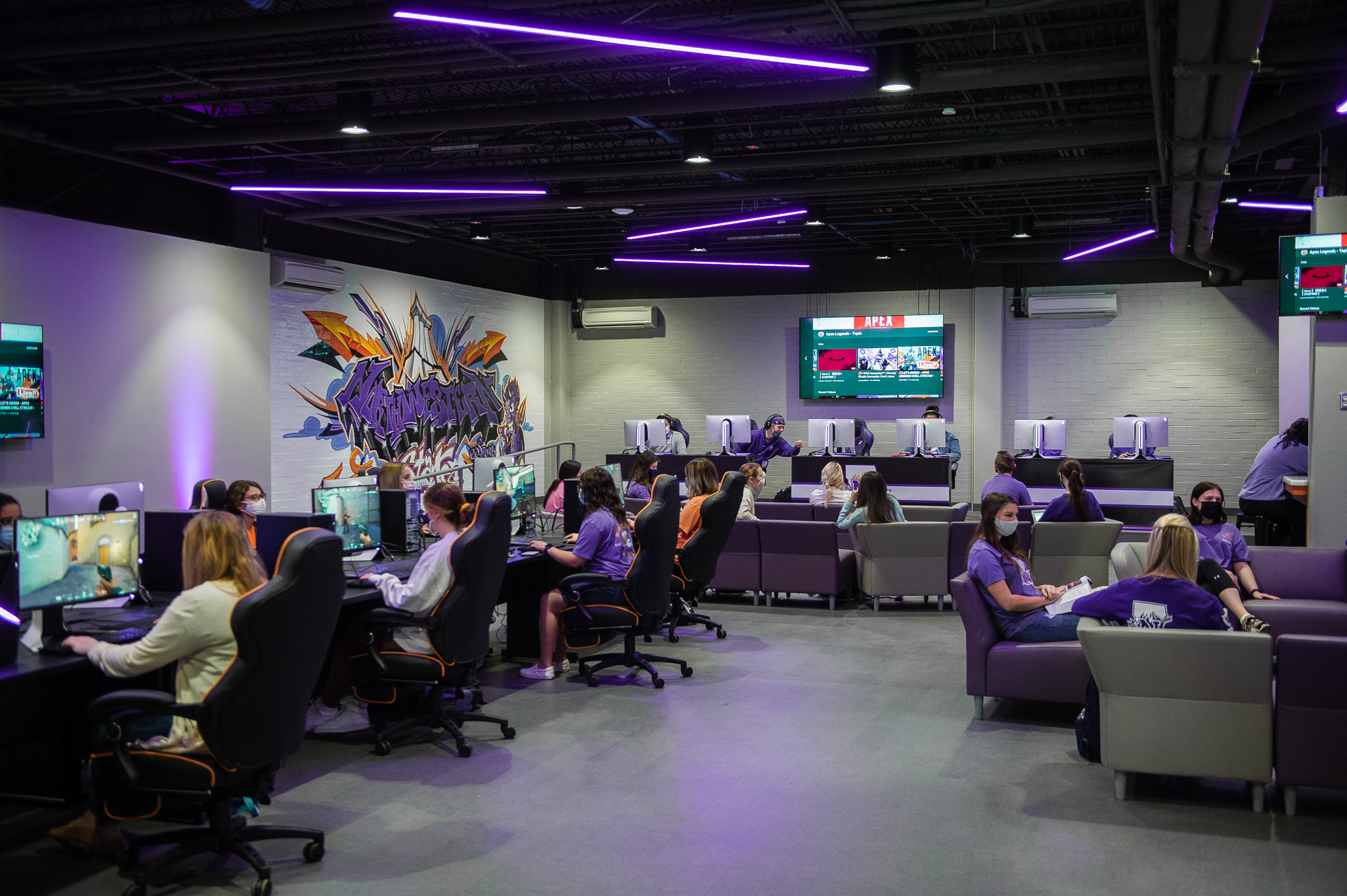 In the NSU Esports Venue, some students game at desktop PCs while others relax and chat with each other on the lounge furniture.