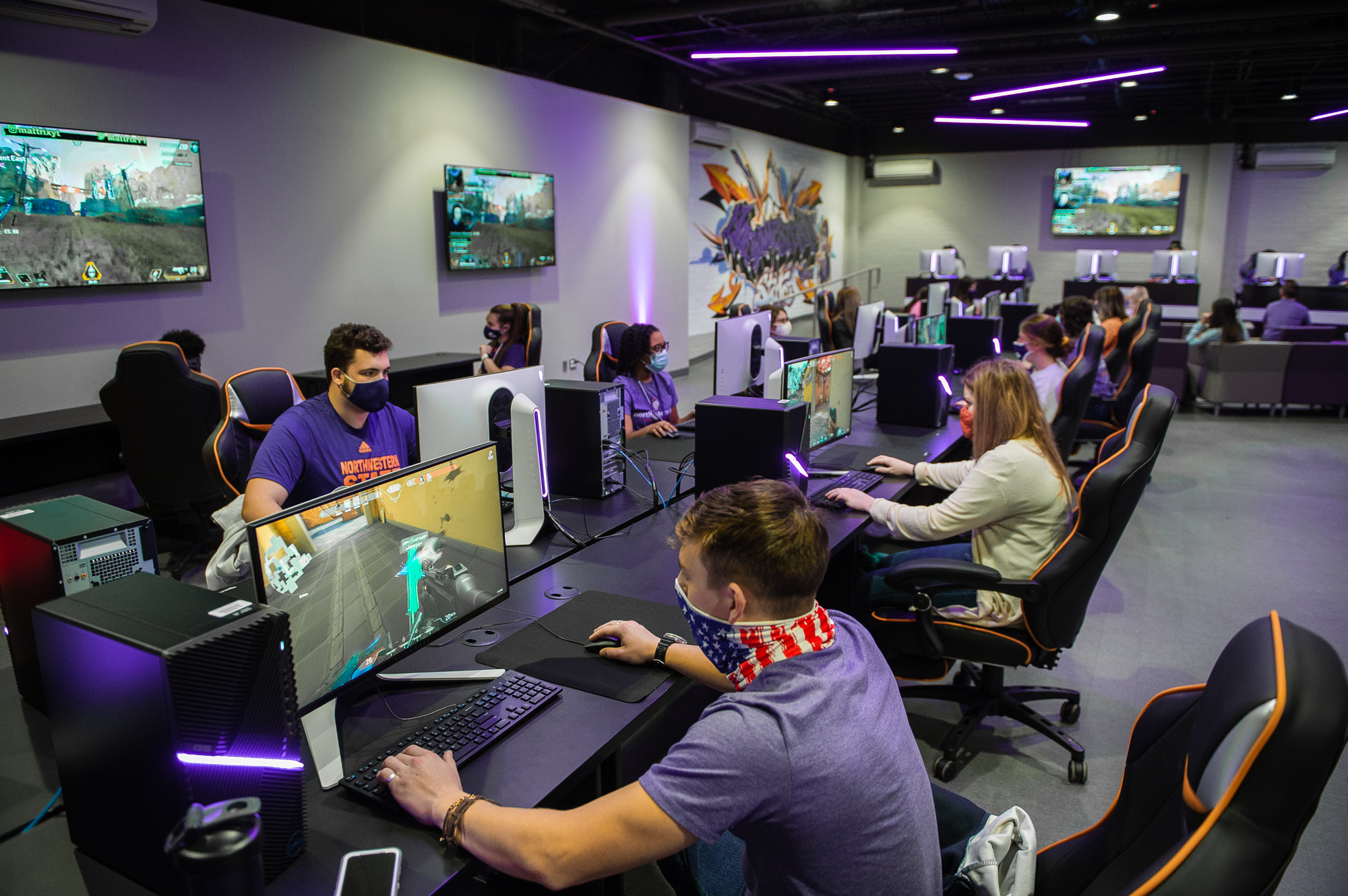 Students play a first-person shooter game at desktop PCs in the NSU Esports Venue.