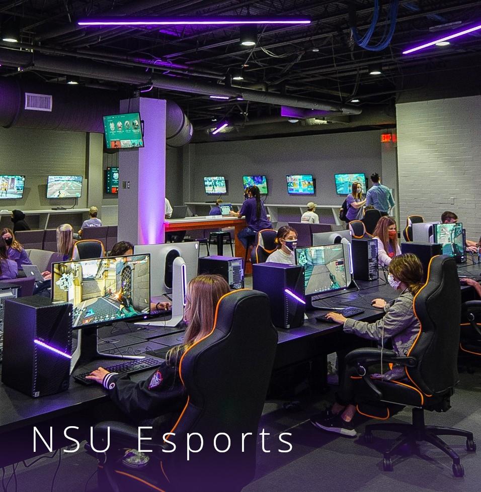Masked students sit in a purple-lit computer lab engaging in a gaming competition.